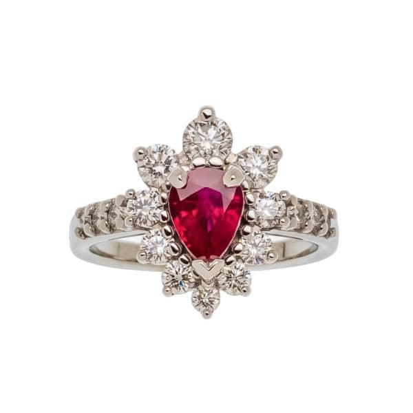 Majesty est une bague en or blanc avec en son centre un rubis rouge taille poire et des diamants formant les pétales. Diamants sur le corps. - face