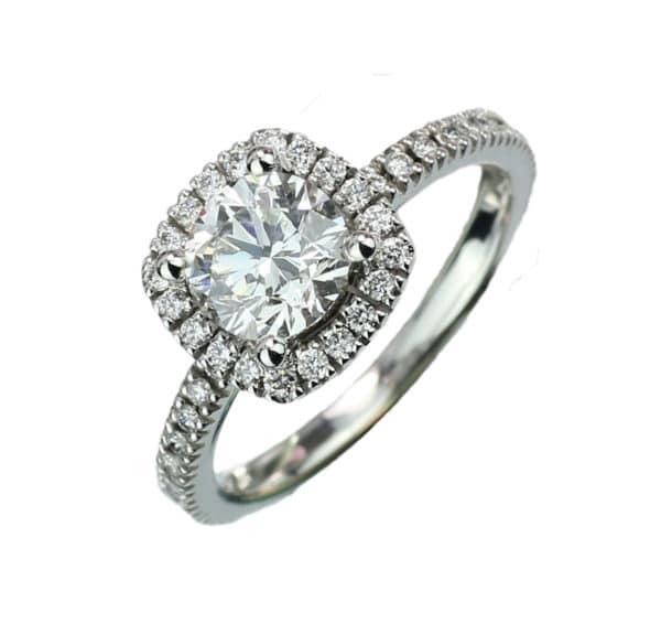 Moon White est une bague Joaillerie entourage en or blanc 750/1000ème avec au centre un diamant et accompagné de diamants sur le corps de bague. - coté