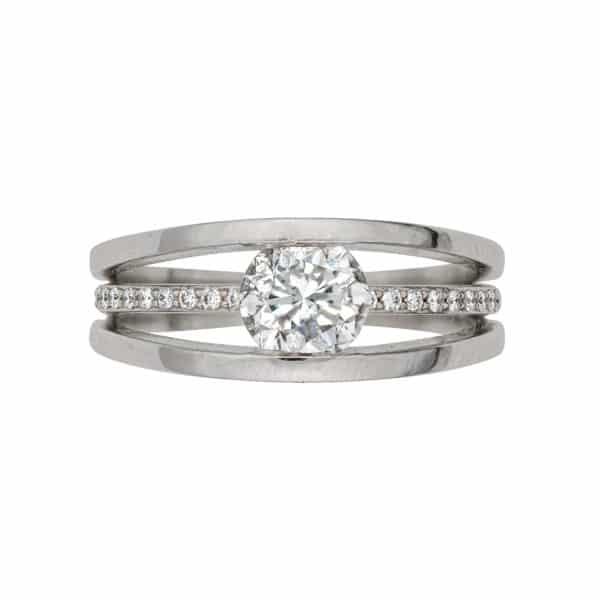 La bague Ellipse Joaillerie est en or blanc 750/1000ème au centre un Diamant taille brillant. Accompagné de Diamants sur le corps de bague.