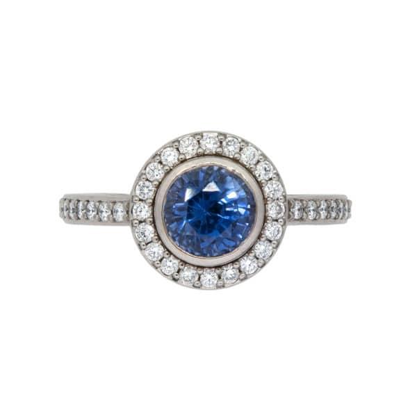 Bague Or Blanc avec Saphir Bleu entouré de diamants. Le corps de la bague contient également des diamants.