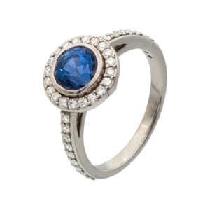 Bague Or Blanc avec Saphir Bleu entouré de diamants. Le corps de la bague contient également des diamants. Vue oblique