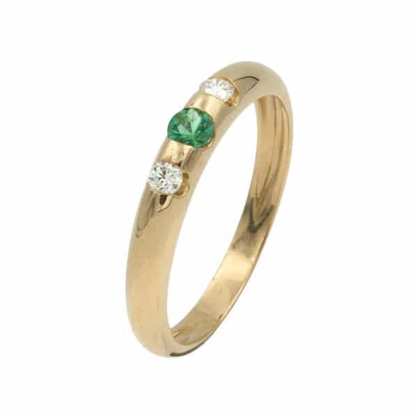 Lumina est une bague en or jaune 750/1000èmen avec au centre une Émeraude taille brillant et sur les cotés de 2 Diamants taille brillant. - oblique