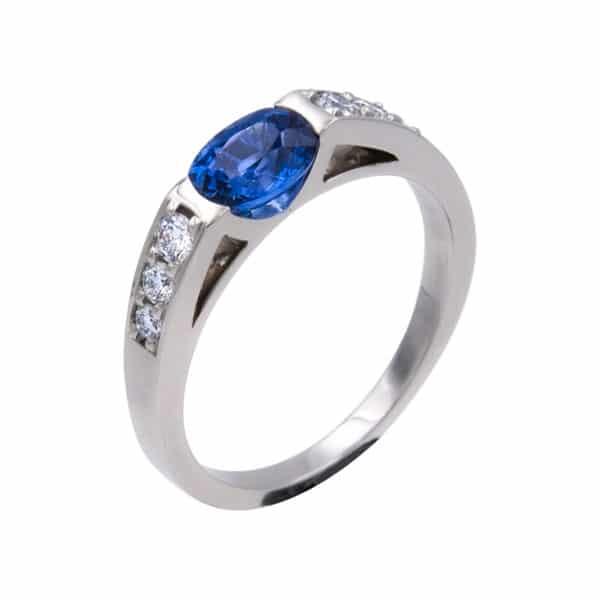 Célesta est une bague en or blanc 750/1000ème avec au centre un Saphir taille Ovale. Accompagnée sur les cotésde 6 Diamants taille brillant. - oblique