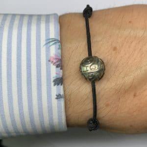 """Tahiti Nui est un bracelet avec une perle de Tahiti """"gravé"""". Le bracelet est en nylon couleur noir. Réglable entre 15.0cm à 25.cm de longueur. - Poignet Zoom"""