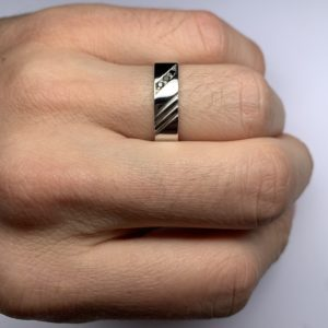 Racer est une bague en argent 925/1000ème de forme carré avec 3 stries. Elle est accompagnée de 3 Diamants noirs. - Sur main